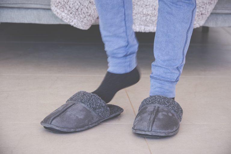 Female feet putting on slippers, standing on tiled floor in bedroom.